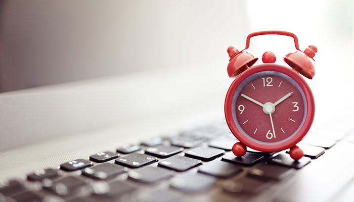 Red clock placed on a keyboard
