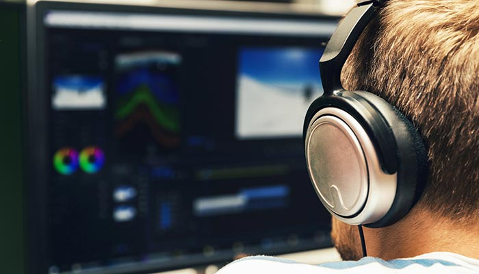 Man with headphones on at an editing desk